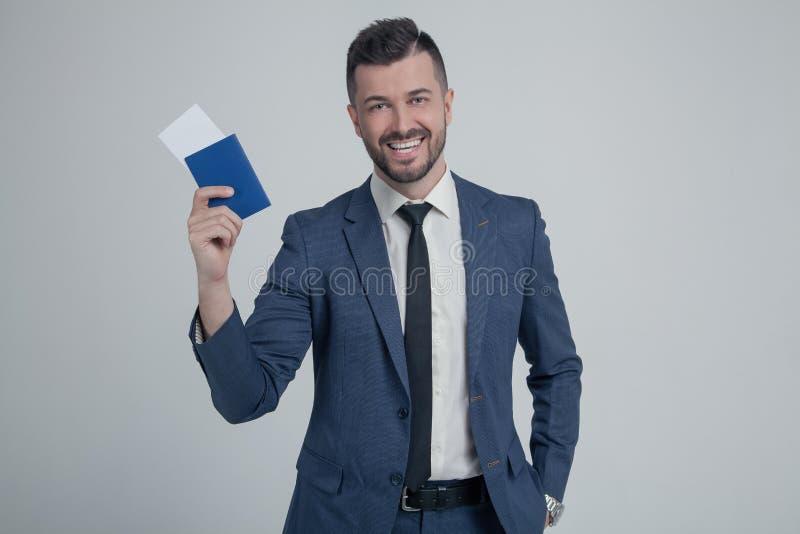Uśmiechnięty młody biznesowy mężczyzna w klasycznym czarnym kostiumu, koszulowy chwyta paszport, abordaż przepustki bilet odizolo fotografia royalty free