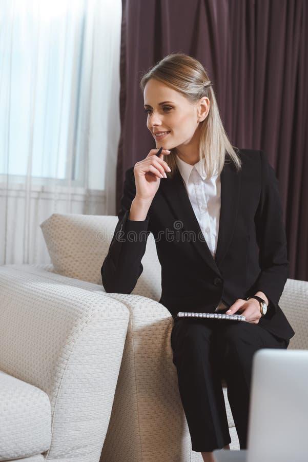 uśmiechnięty młody bizneswoman bierze notatki podczas gdy siedzący zdjęcie stock