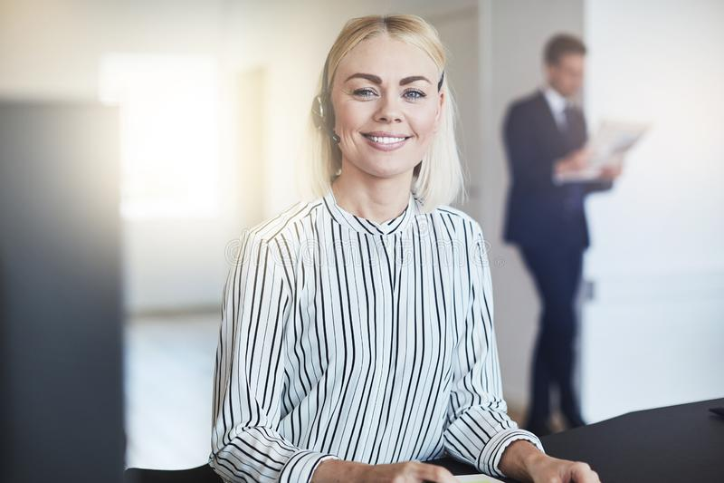 Uśmiechnięty młody bizneswoman jest ubranym słuchawki przy jej biurowym biurkiem fotografia royalty free
