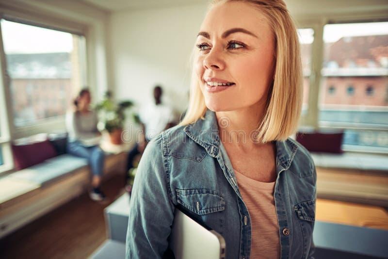 Uśmiechnięty młody bizneswoman niesie laptop w biurze zdjęcia royalty free
