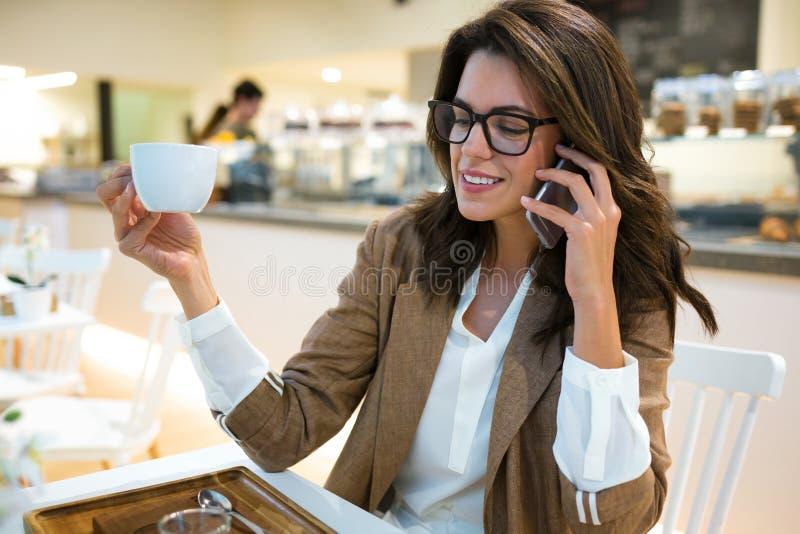 Uśmiechnięty młody bizneswoman opowiada z jej telefonem komórkowym w sklepie z kawą zdjęcie stock