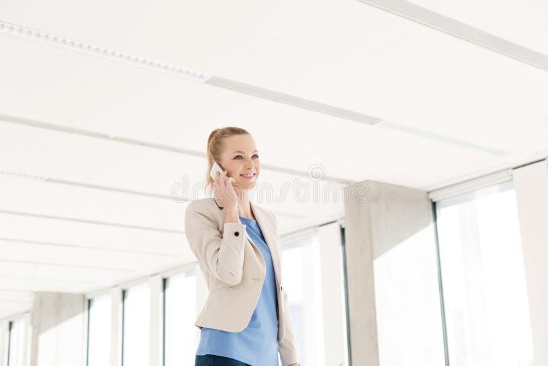 Uśmiechnięty młody bizneswoman używa telefon komórkowego w nowym biurze fotografia stock
