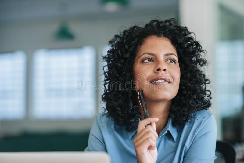 Uśmiechnięty młody bizneswoman w myśli przy jej biurowym biurkiem głęboko obraz stock