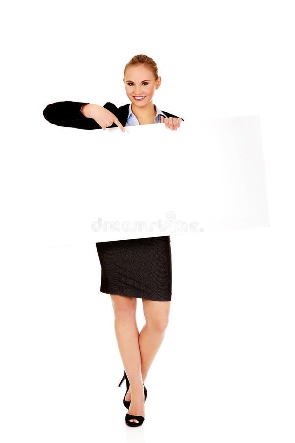 Uśmiechnięty młody bizneswomanu mienia pustego miejsca sztandar zdjęcie royalty free