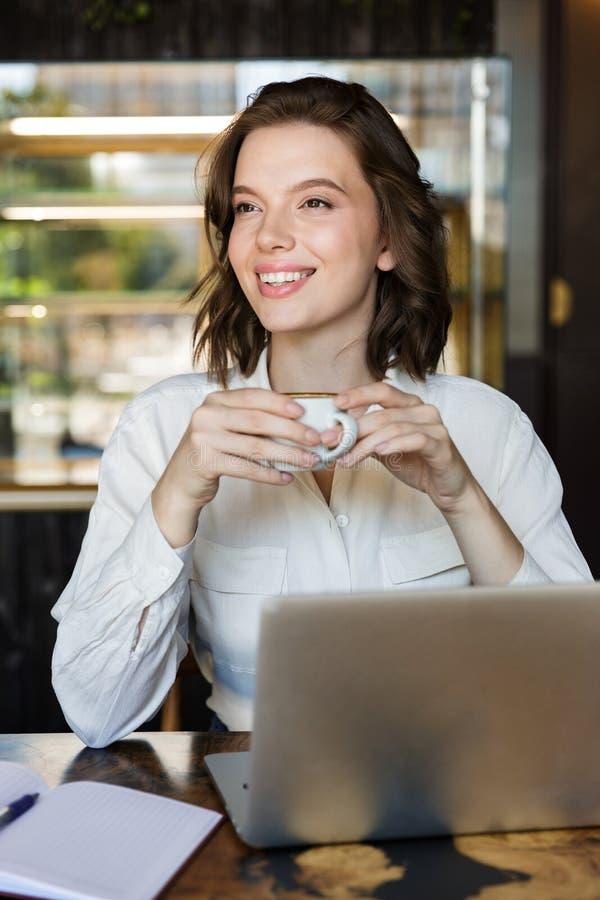 Uśmiechnięty młody bizneswomanu obsiadanie przy kawiarnią indoors fotografia royalty free