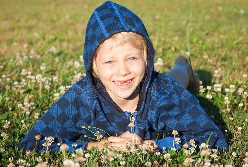 Uśmiechnięty młody chłopiec lying on the beach w trawy ono uśmiecha się zdjęcia stock