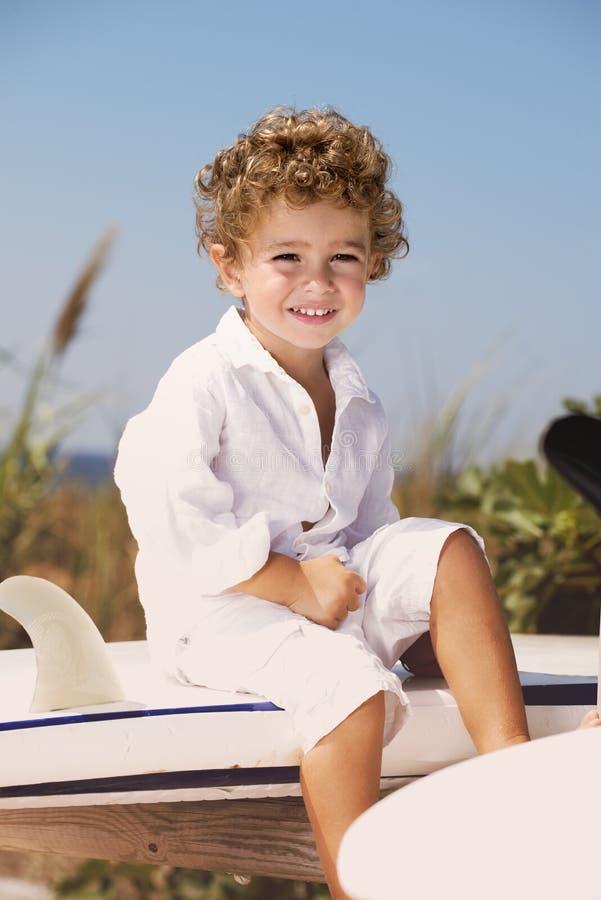 Uśmiechnięty młody chłopiec obsiadanie na surfboard stojaku obraz stock