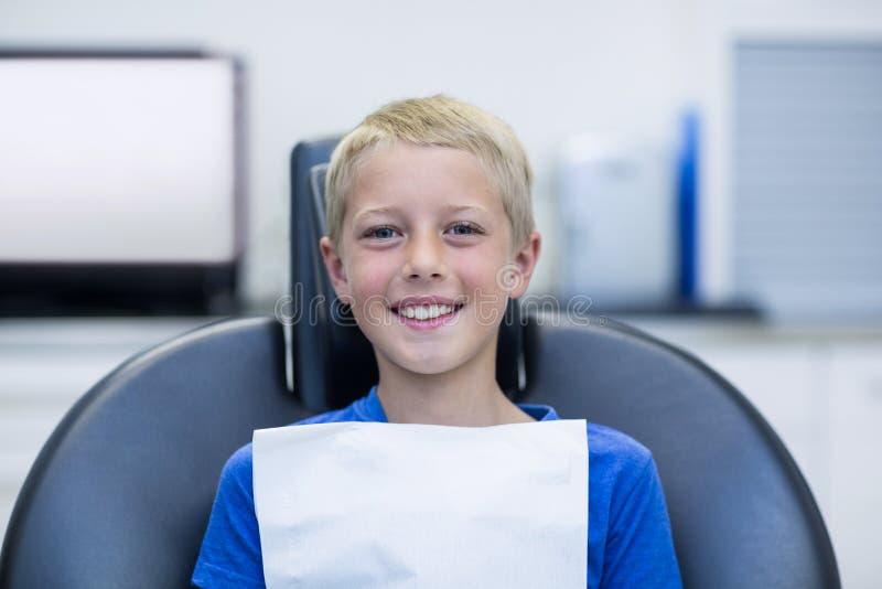 Uśmiechnięty młody cierpliwy obsiadanie na dentysty krześle obraz stock