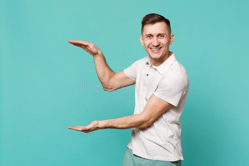 Uśmiechnięty młody człowiek gestykuluje w przypadkowych ubraniach demonstrujący rozmiar z pionowo workspace odizolowywającym na b fotografia stock
