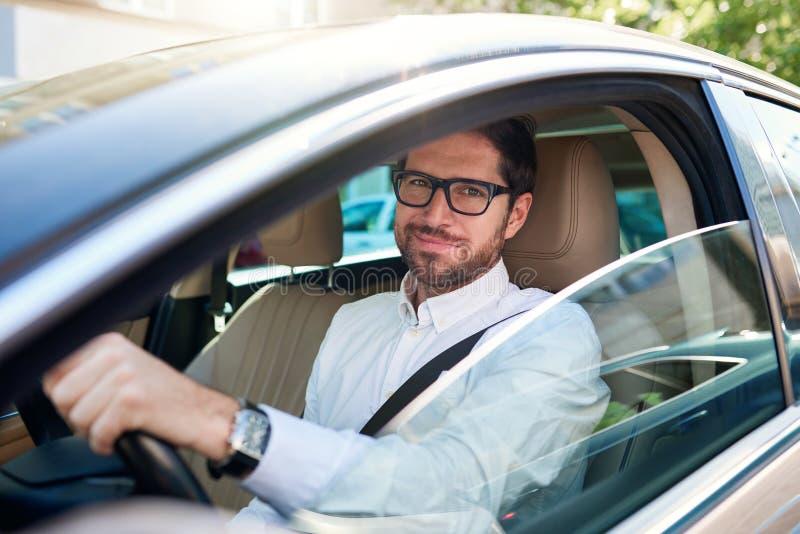 Uśmiechnięty młody człowiek jedzie jego samochód przez miasto ulic zdjęcia stock