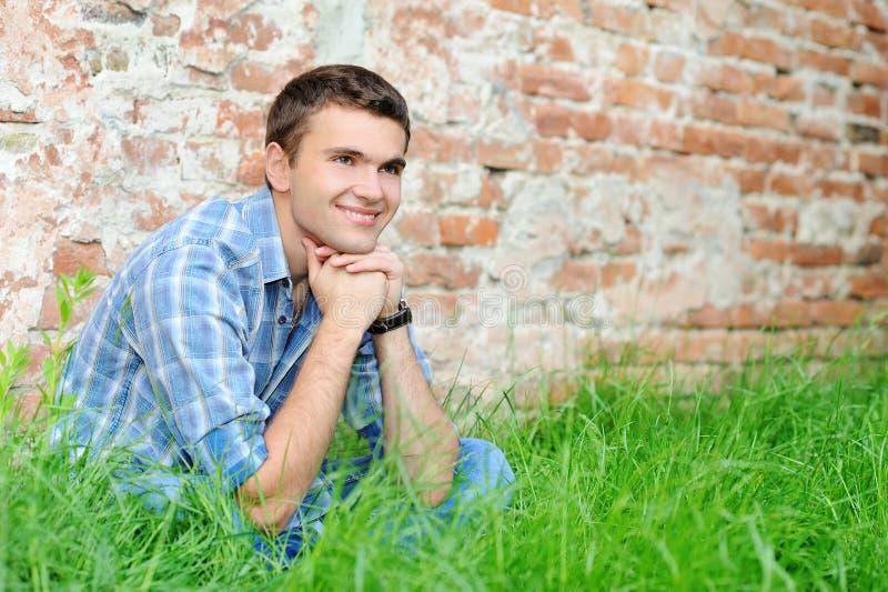 Uśmiechnięty młody człowiek na trawie obraz stock