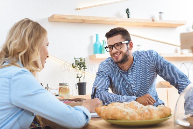 uśmiechnięty młody człowiek patrzeje kelnerki bierze notatki w eyeglasses zdjęcie stock