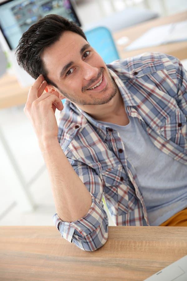 Uśmiechnięty młody człowiek przy biurem zdjęcie stock