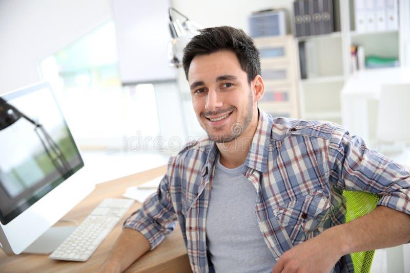Uśmiechnięty młody człowiek przy biurem obraz stock