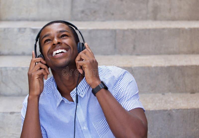 Uśmiechnięty młody człowiek słucha muzyka na hełmofonach fotografia royalty free