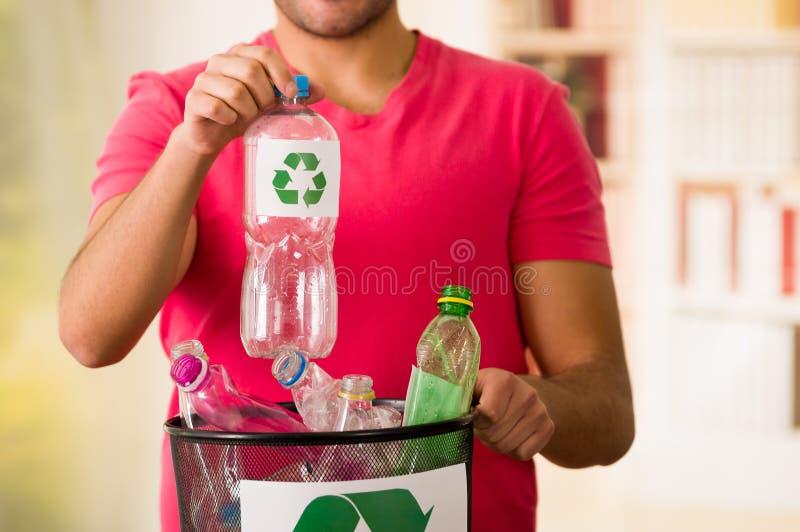 Uśmiechnięty młody człowiek stawia plastikową butelkę wśrodku małego czarnego śmieciarskiego poborcy klingeryt pełno, przetwarza  obrazy stock