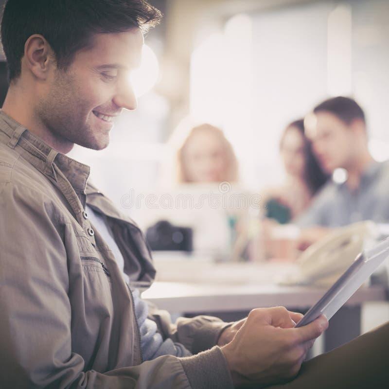 Uśmiechnięty młody człowiek używa cyfrową pastylkę zdjęcie royalty free