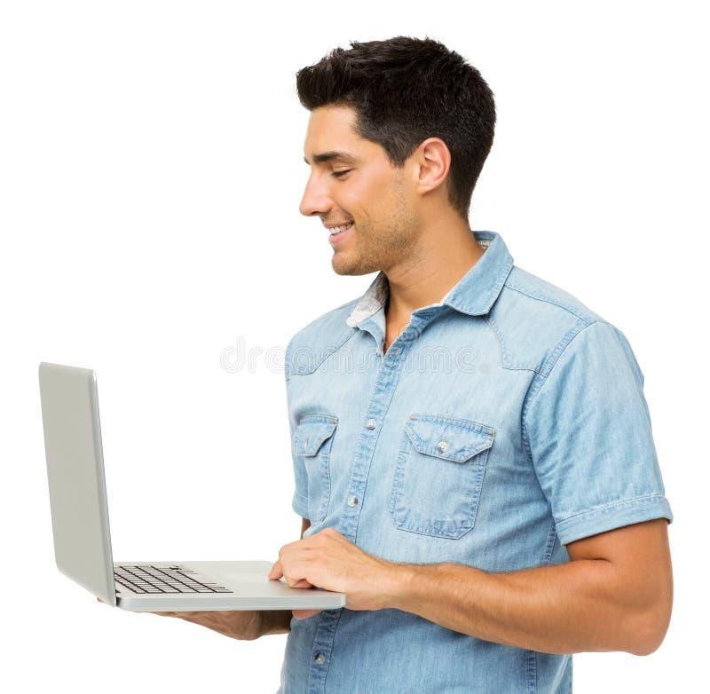 Uśmiechnięty młody człowiek Używa laptop fotografia stock