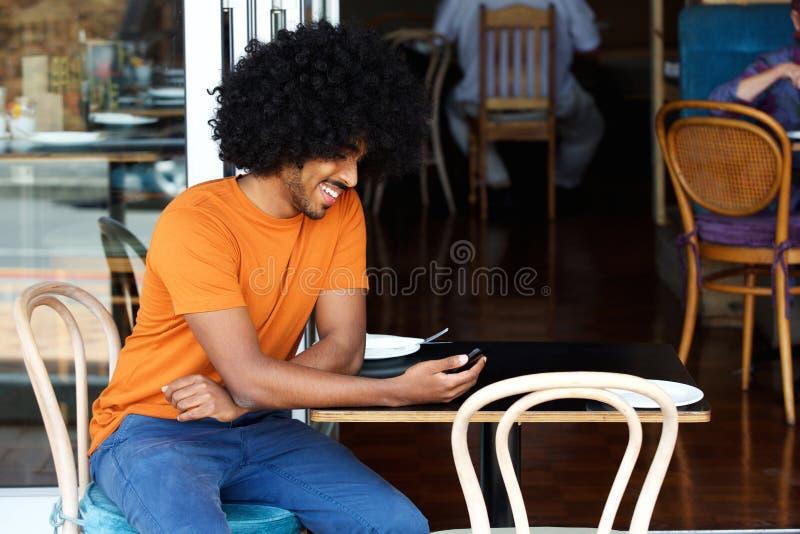 Uśmiechnięty młody człowiek używa telefon komórkowego przy kawiarnią obraz stock