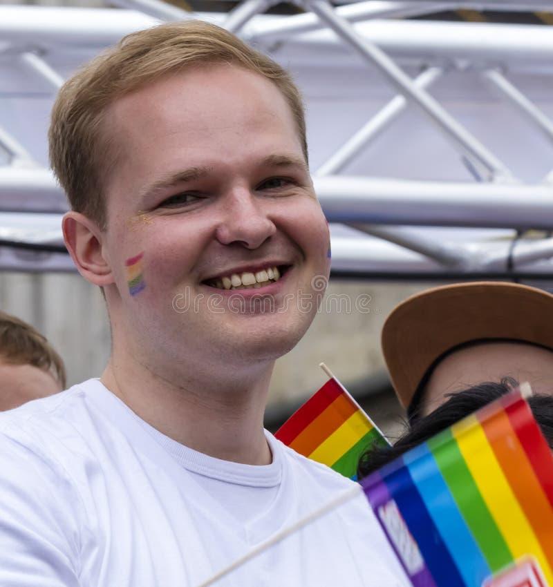 2019: Uśmiechnięty młody człowiek uczęszcza Gay Pride paradę także znać jako Christopher dnia Uliczny CSD w Monachium z tęczy fla obraz stock