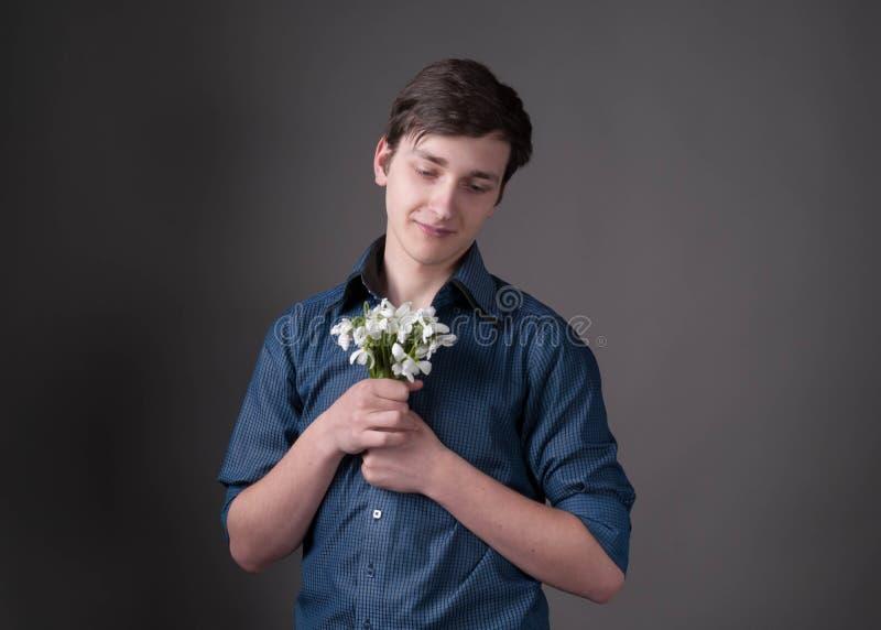 uśmiechnięty młody człowiek w błękitnym koszulowym mieniu i patrzeć bukiet z białymi śnieżyczkami zdjęcie royalty free
