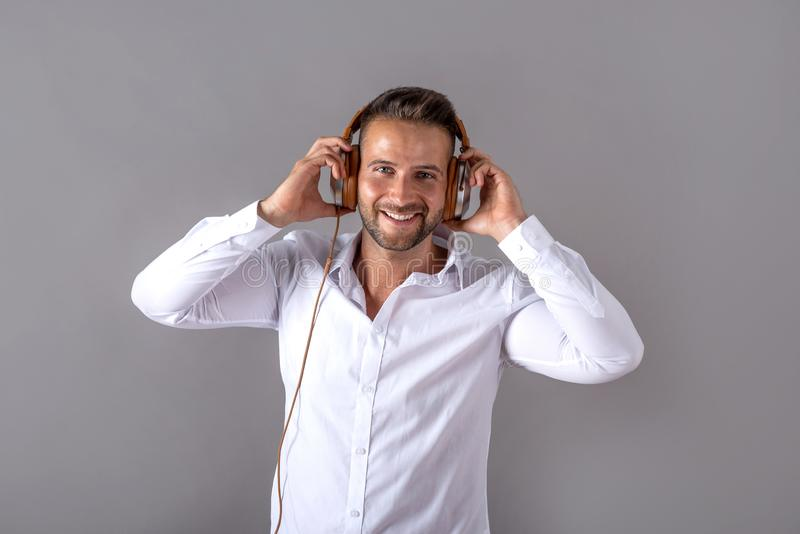 Uśmiechnięty młody człowiek w białym koszulowym słuchaniu muzyka fotografia royalty free