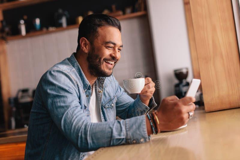 Uśmiechnięty młody człowiek w cukiernianym używa telefonie komórkowym zdjęcie royalty free