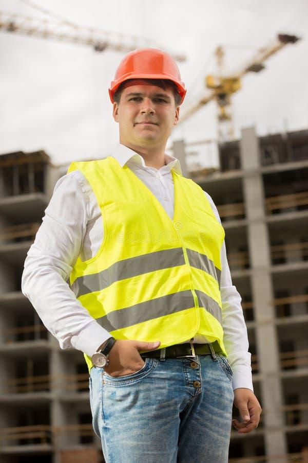 Uśmiechnięty młody człowiek w czerwonej hardhat i zieleni kamizelki zbawczej pozyci na placu budowy zdjęcia stock