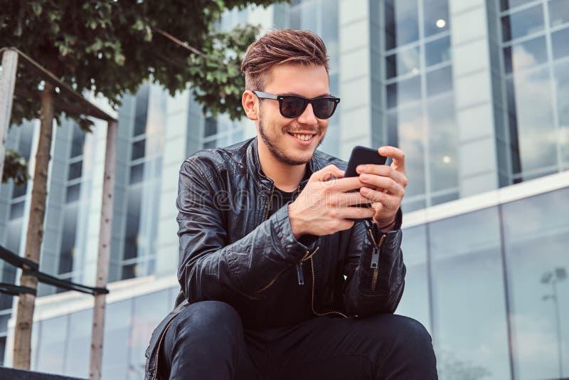 Uśmiechnięty młody człowiek w okularach przeciwsłonecznych z eleganckim włosy ubierał w czarnej skórzanej kurtce używać smartphon zdjęcie stock