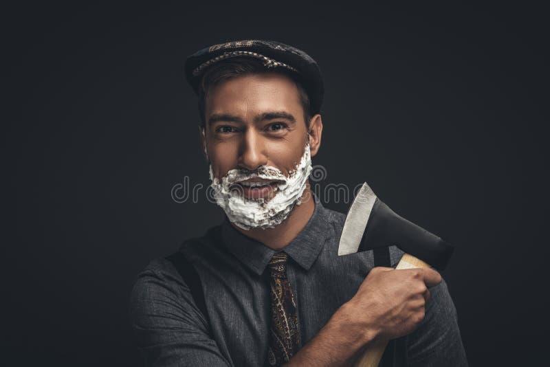 Uśmiechnięty młody człowiek w płaskiej nakrętce z golenie śmietanką na jego twarzy i, przygotowywa jego brodę zdjęcia royalty free