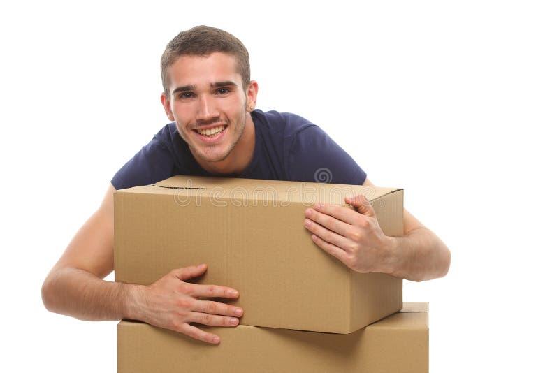 Uśmiechnięty młody człowiek z dużymi pudełkami Na biały tle zdjęcia royalty free