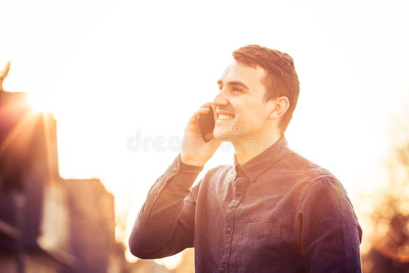 Uśmiechnięty młody człowiek z telefonem komórkowym plenerowym w zmierzchu fotografia stock