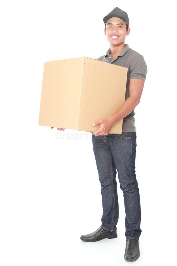Uśmiechnięty młody doręczeniowy mężczyzna trzyma cardbox obraz stock