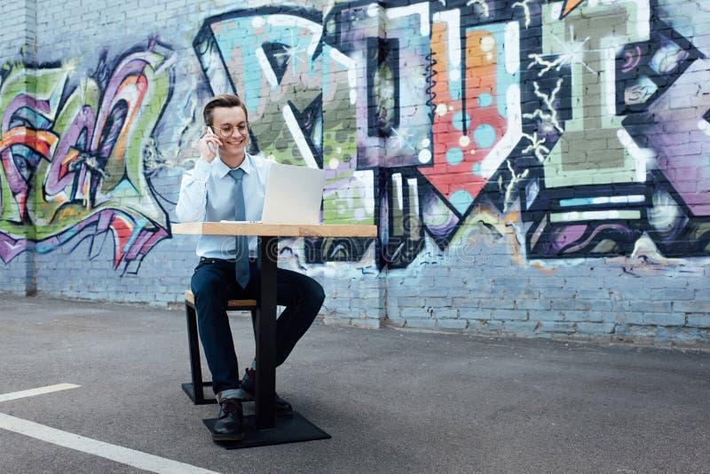 uśmiechnięty młody freelancer opowiada smartphone i używa laptop w eyeglasses podczas gdy siedzący obraz stock