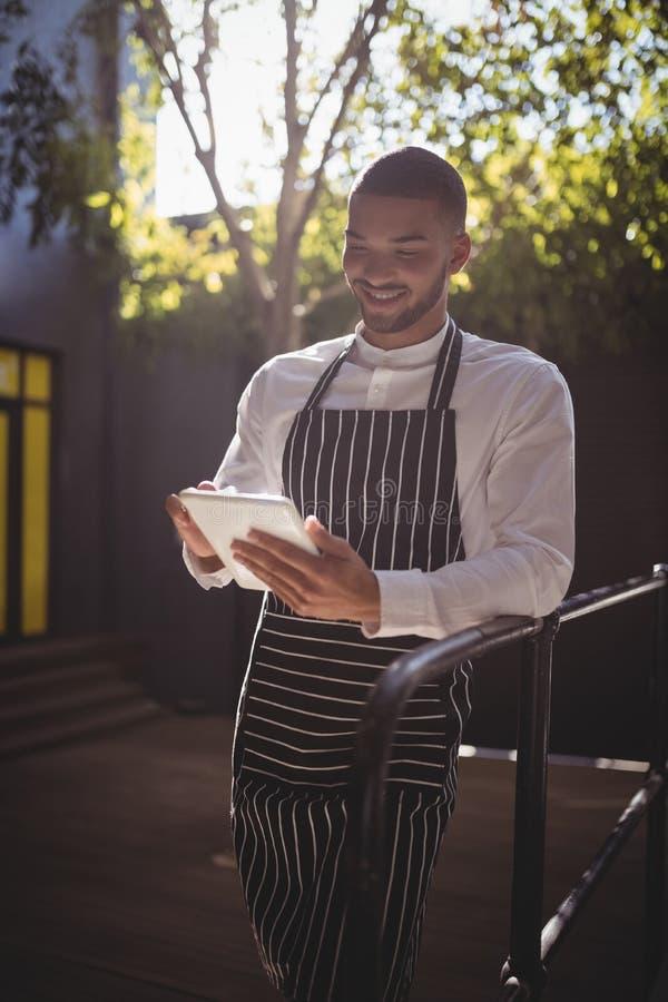 Uśmiechnięty młody kelner używa cyfrową pastylkę podczas gdy opierający na ostro protestować zdjęcie royalty free