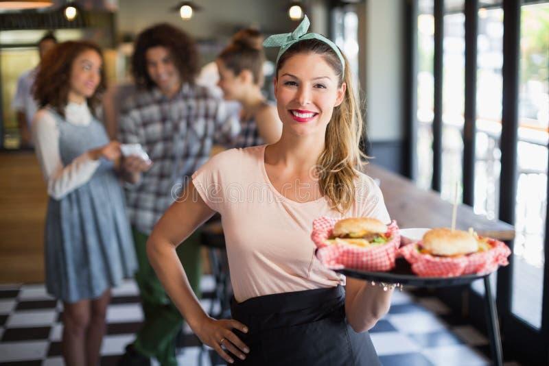 Uśmiechnięty młody kelnerki porci hamburger w restauraci zdjęcie stock