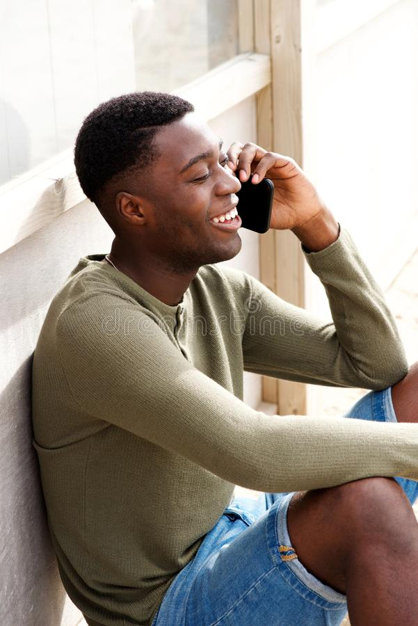 Uśmiechnięty młody murzyn opowiada na telefonie komórkowym outdoors zdjęcia stock