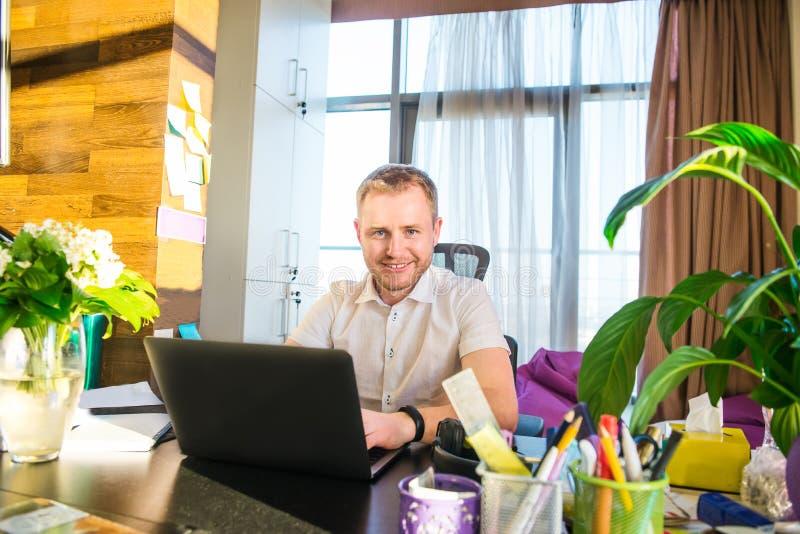 Uśmiechnięty młody przedsiębiorca patrzeje kamerę przy jego miejscem pracy Pomyślny pozytywny biznesmen przy jego nowym nowożytny fotografia stock