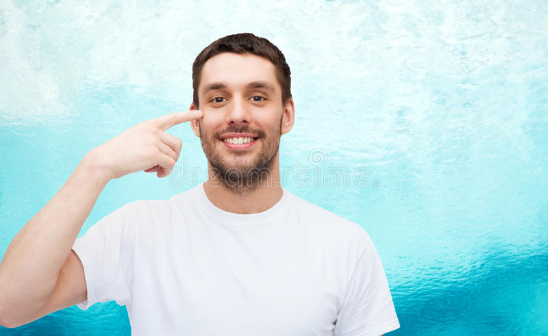 Uśmiechnięty młody przystojny mężczyzna wskazuje oczy zdjęcie royalty free