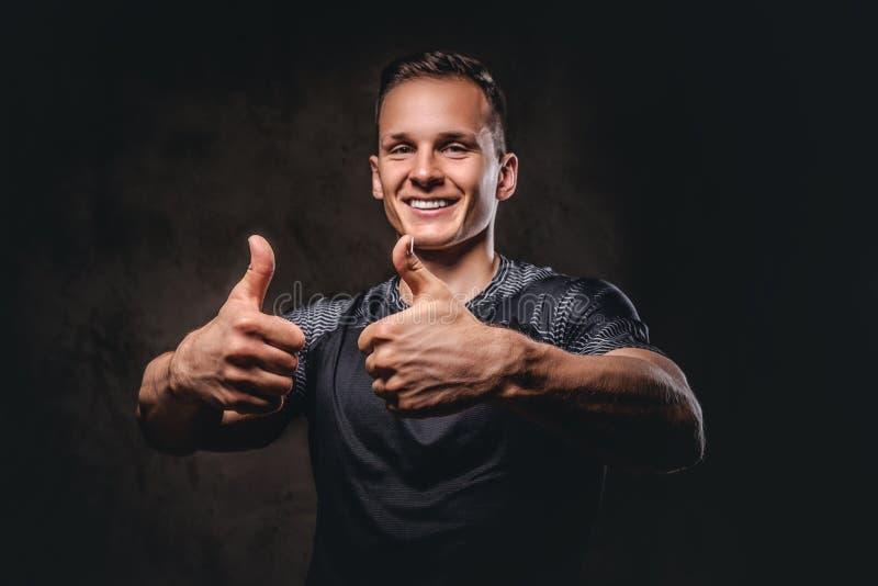 Uśmiechnięty młody sportowiec pokazuje aprobaty na ciemnym tle obraz stock