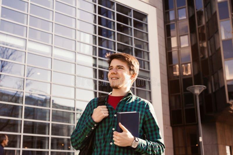 Uśmiechnięty młody studencki mężczyzna trzyma książkę i torbę na universi obraz stock
