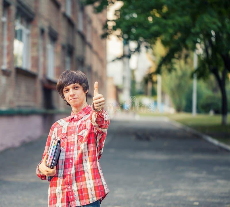 Uśmiechnięty młody studencki mężczyzna trzyma książkę, pastylkę i aprobaty, przeciw miastu obraz royalty free