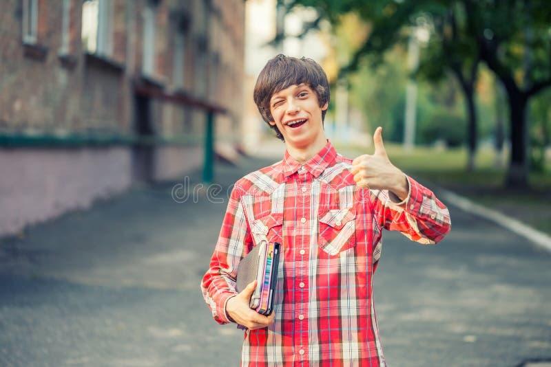 Uśmiechnięty młody studencki mężczyzna trzyma książkę, pastylkę i aprobaty, przeciw miastu obrazy royalty free