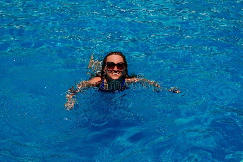 Uśmiechnięty młody szczęśliwy kobiety dopłynięcie w basenie z błękitne wody obraz royalty free