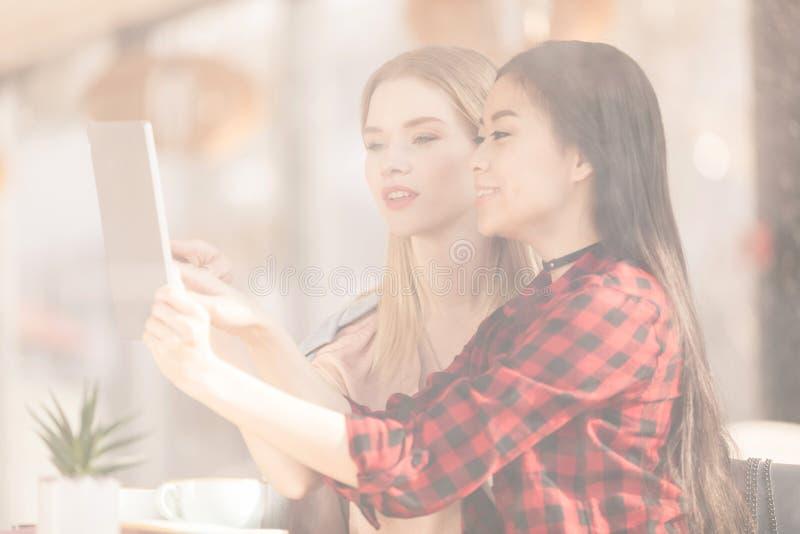 Uśmiechnięty młodych kobiet pić kawowy wpólnie i używać cyfrową pastylki kawę fotografia stock