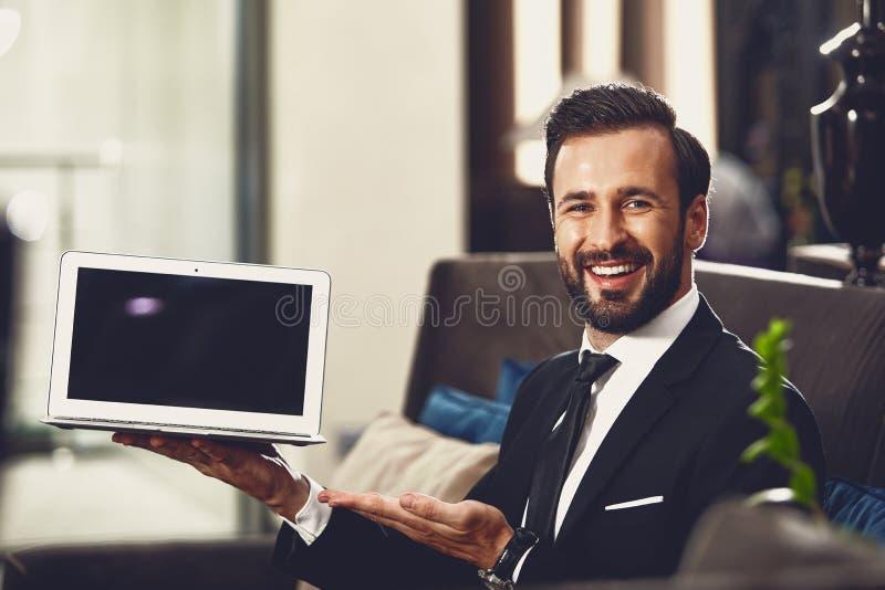 UÅ›miechniÄ™ty mÅ'odzieniec podczas prezentacji swojego laptopa zdjęcia stock