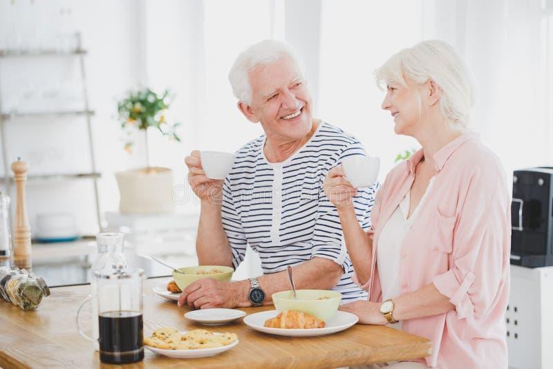 Uśmiechnięty małżeństwo starsze osoby je śniadanie zdjęcia royalty free