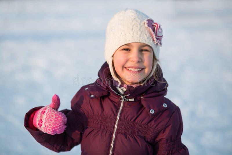 Uśmiechnięty małej dziewczynki łyżwiarstwo przy lodowiskiem w zimie zdjęcia royalty free