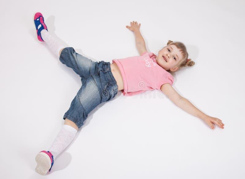 Uśmiechnięty małej dziewczynki lying on the beach na seansu kciuku i podłoga up zdjęcia stock