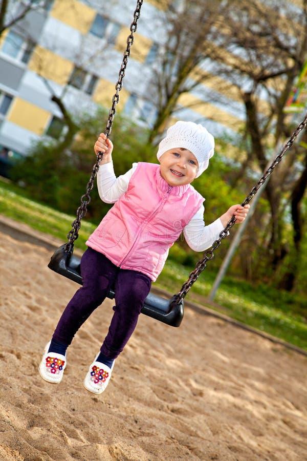 Uśmiechnięty małej dziewczynki obsiadanie na huśtawce obraz royalty free